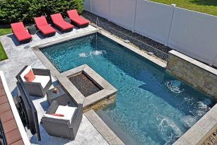 Overview of pool with fire pit and water features and patio seating